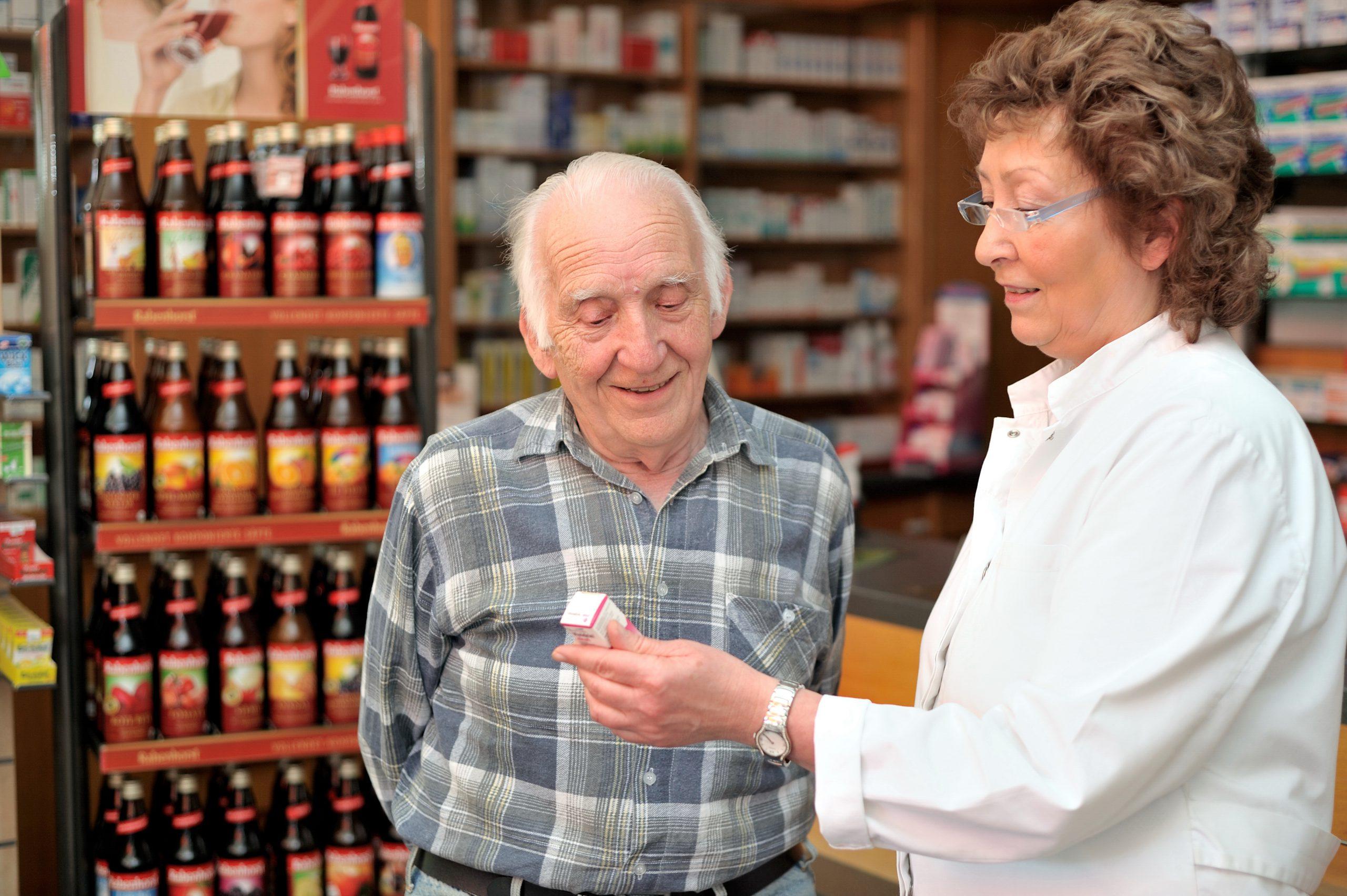 Apothekerin berät einen älteren Kunden